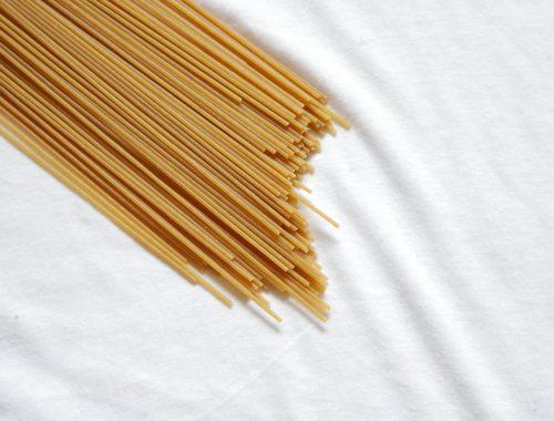 Spaghetti crudi messi in diagonale su sfondo bianco