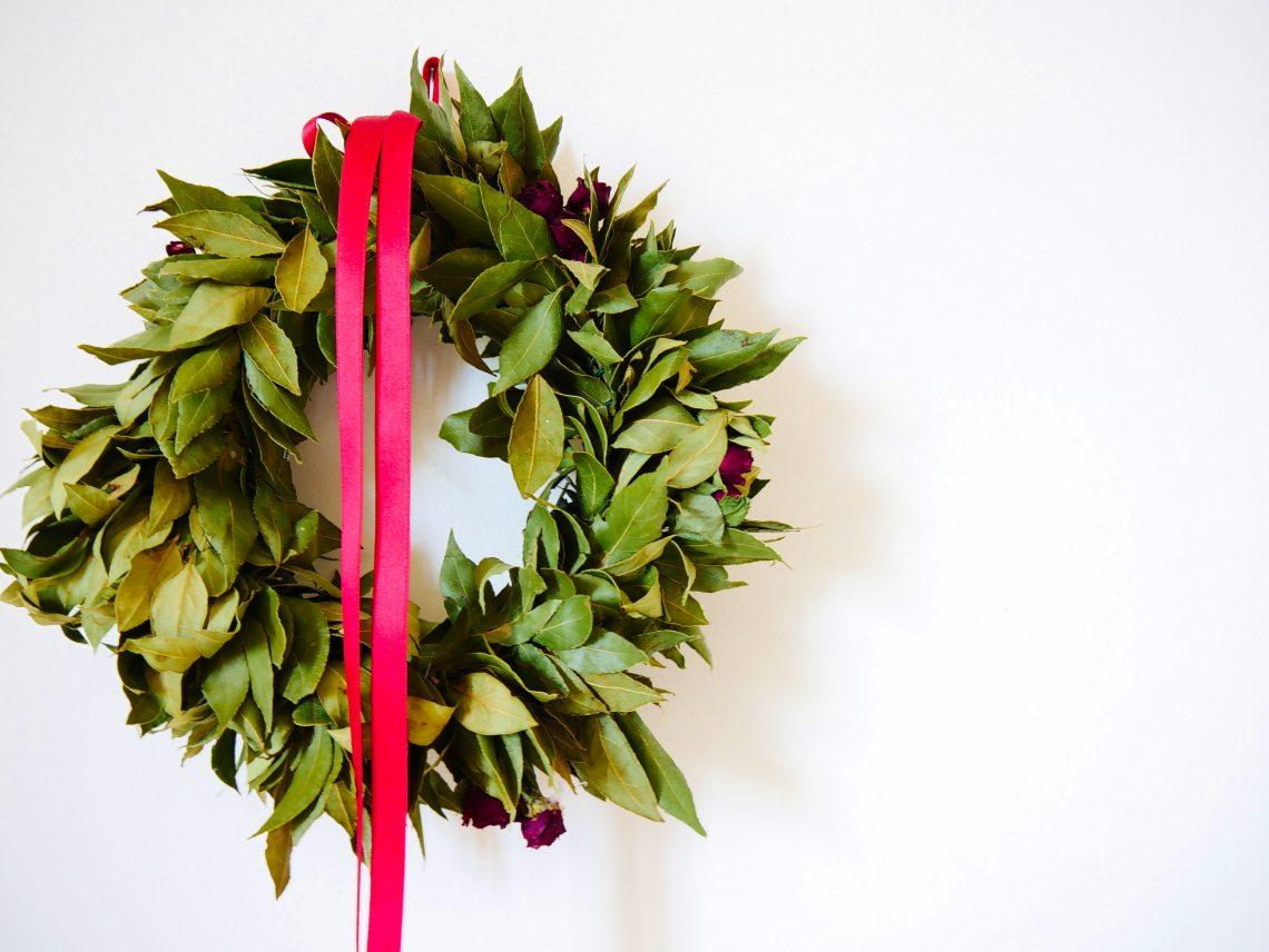 Una corona di alloro con un nastro rosso appesa al muro