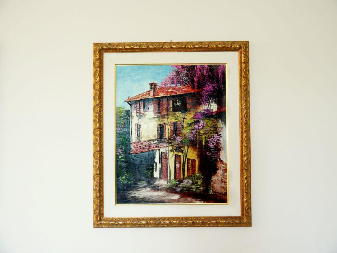 Un quadro che raffigura una casa di campagna è appeso a un muro   Tema: trovare casa per studenti in Germania