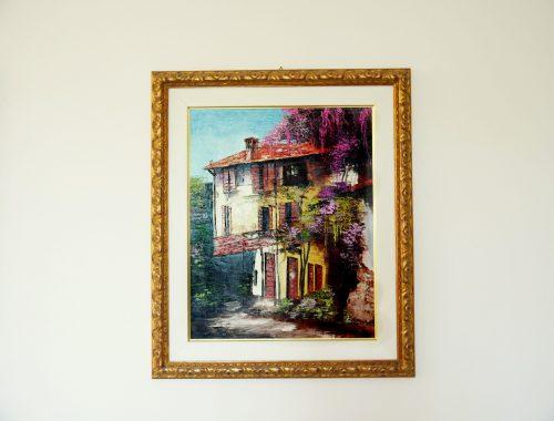 Un quadro che raffigura una casa di campagna è appeso a un muro | Tema: trovare casa per studenti in Germania