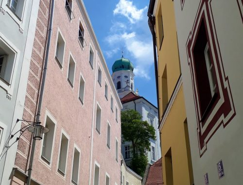 Scorcio di un vicolo in cui si vede la torre del duomo di Passavia