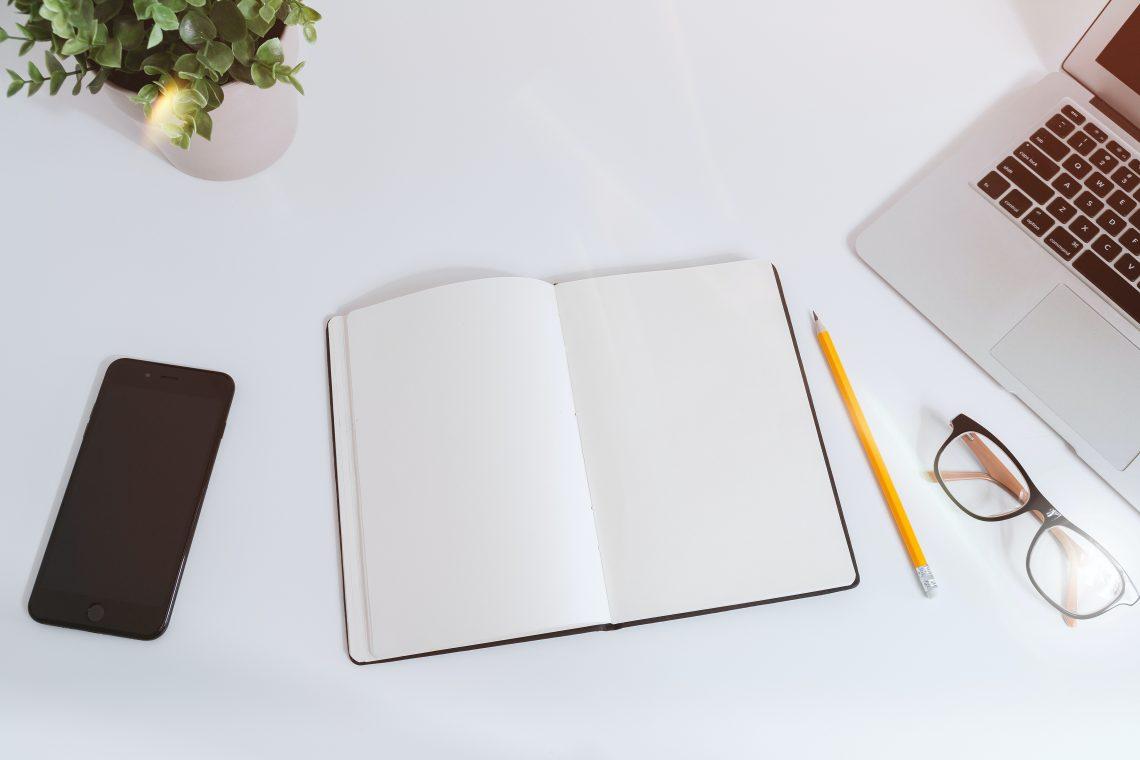Un quaderno, una penna, un cellulare, un computer e un paio di occhiali su una scrivania | Photo by JESHOOTS.COM on Unsplash