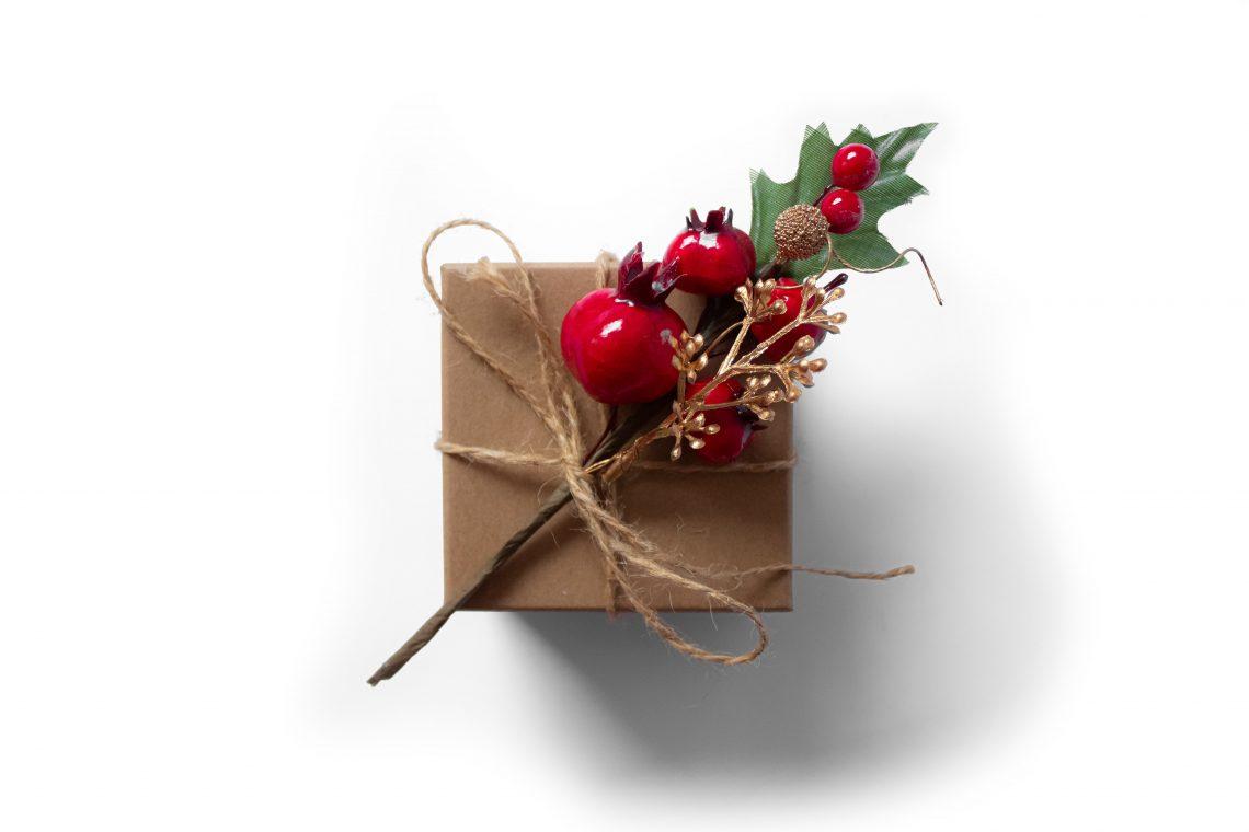 Un pacchetto regalo rivestito di carta marrone e decorato con un ramo di melograno | Photo by Tijana Drndarski on Unsplash