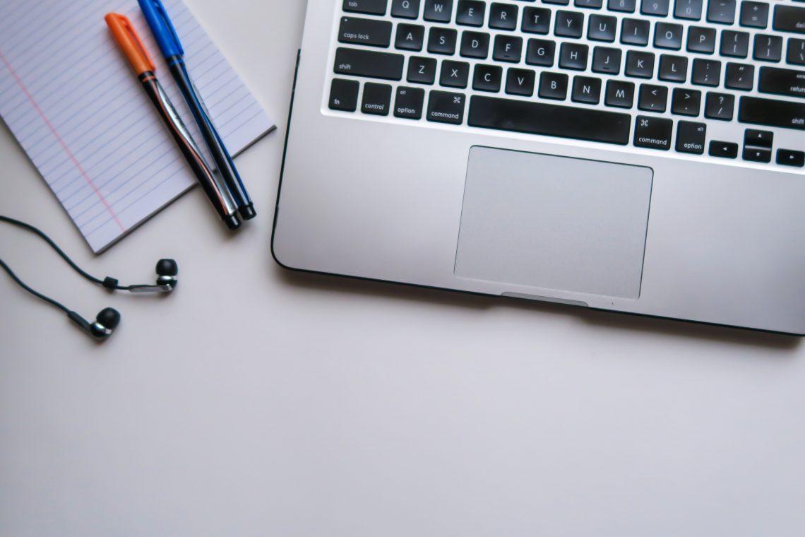 Un computer portatile, degli auricolari, un foglio e delle penne su una scrivania   Photo by Maya Maceka on Unsplash