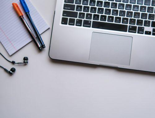 Un computer portatile, degli auricolari, un foglio e delle penne su una scrivania | Photo by Maya Maceka on Unsplash