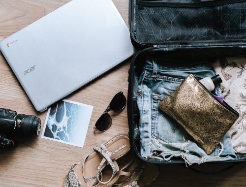 Una valigia aperta con oggetti sparsi: un computer, una macchina fotografica, una foto, occhiali da sole e vestiti | Photo by Anete Lūsiņa on Unsplash
