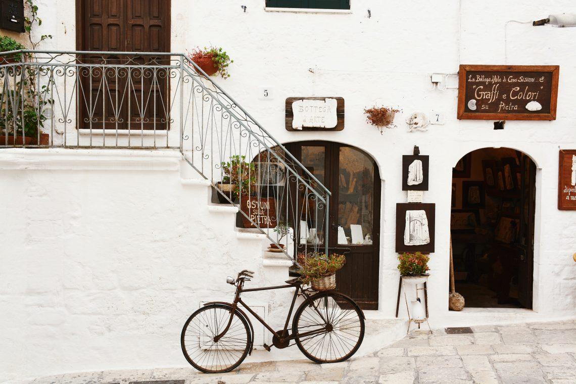 La facciata di un edificio bianco con botteghe e una bicicletta nera appoggiata a una scala | Photo by Bogdan Dada on Unsplash