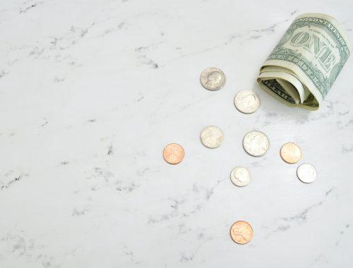 Una banconota da un dollaro e qualche moneta su una superficie di marmo | Photo by Katie Harp on Unsplash