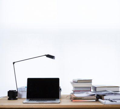 Un computer e dei libri su una scrivania | Photo by freddie marriage on Unsplash
